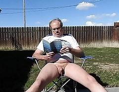 A daddy reading a book and peeing.